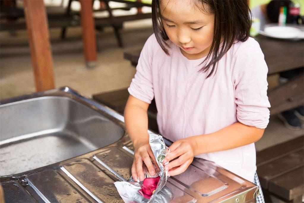 さつまいもをアルミホイルで包む女の子/7歳以上におすすめバーべキューお手伝い