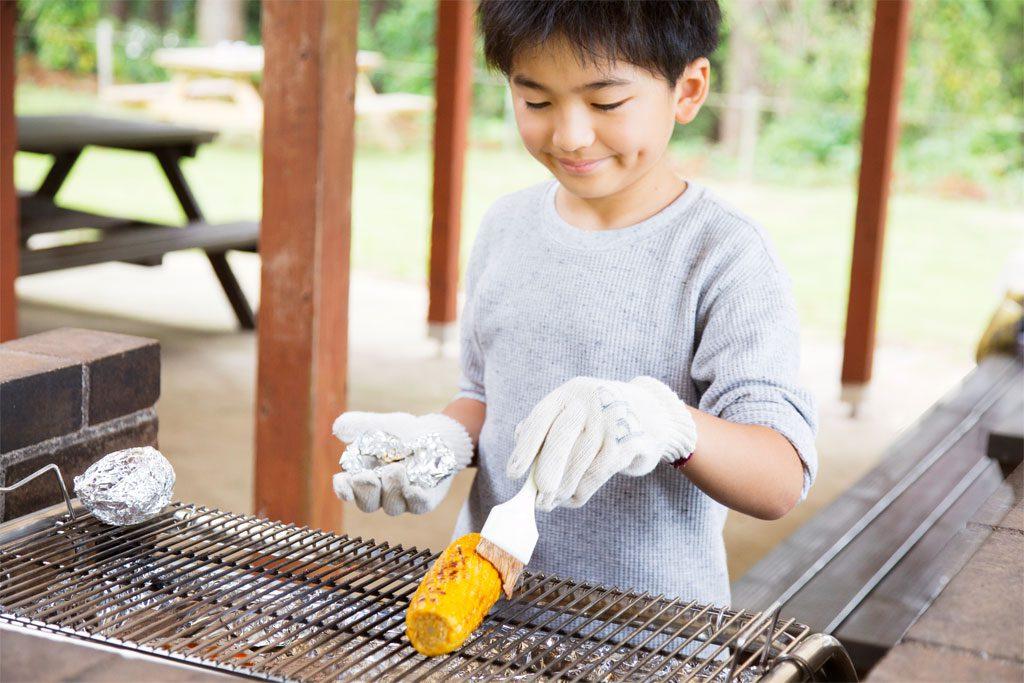 焼きとうもろこしに醤油を塗る男の子/7歳以上におすすめバーべキューお手伝い